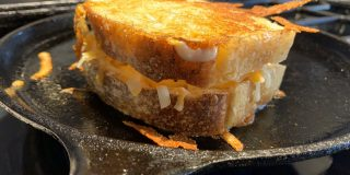 A grilled cheese sandwich on a cast iron gridle.